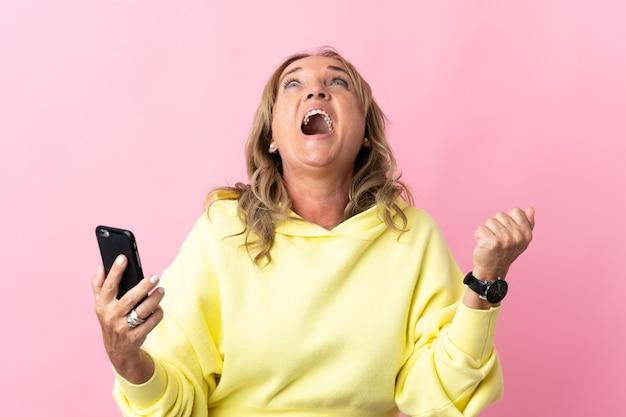 Blonde vrouw van middelbare leeftijd over geïsoleerde roze muur die mobiele telefoon met behulp van en overwinningsgebaar doet