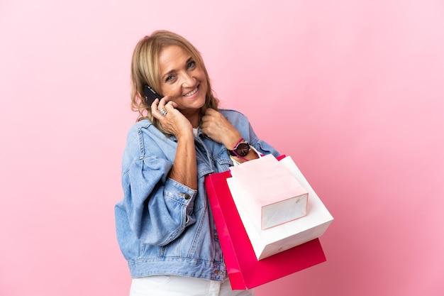 Blonde vrouw van middelbare leeftijd over geïsoleerde roze muur met boodschappentassen en een vriend bellen met haar mobiele telefoon