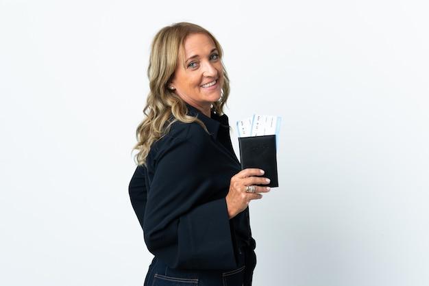 Blonde vrouw van middelbare leeftijd over geïsoleerde witte muur gelukkig in vakantie met paspoort en vliegtickets