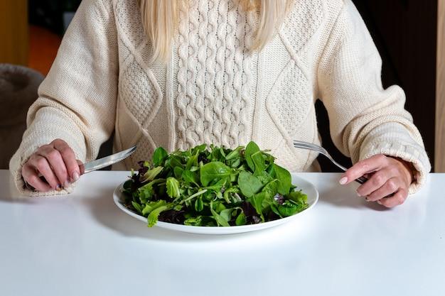 Blonde vrouw van middelbare leeftijd salade eten in de keuken, gezond voedsel concept