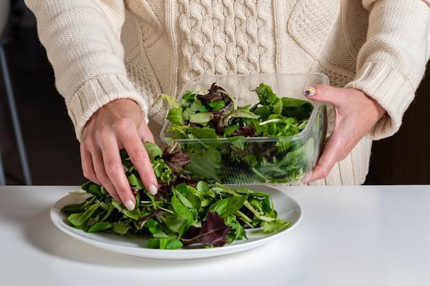Blonde vrouw van middelbare leeftijd voorbereiding van groene salade in de keuken, gezond eten en dieet concept, close-up