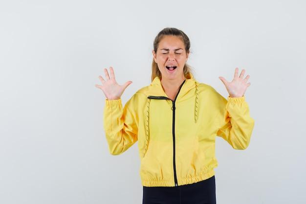 Blonde vrouw verhogen handen in overgave pose terwijl schreeuwen in gele bomberjack en zwarte broek en gekwelde op zoek