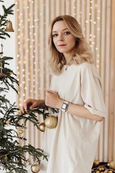 Blonde vrouw versiert dennenboom voor de viering van het nieuwe jaar en kerstmis