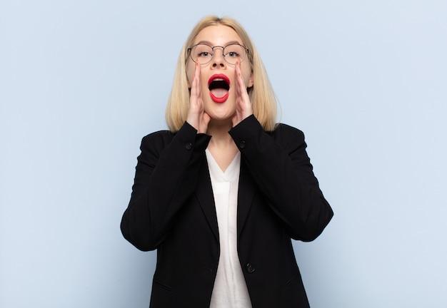 Blonde vrouw voelt zich blij, opgewonden en positief, geeft een grote schreeuw met handen naast de mond, roept