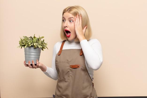 Blonde vrouw voelt zich blij, opgewonden en verrast, opzij kijkend met beide handen op het gezicht