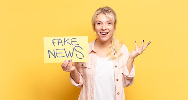 Blonde vrouw voelt zich blij, verrast en opgewekt, lacht met een positieve instelling, realiseert zich een oplossing of idee