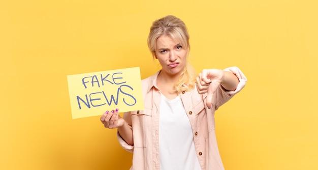 Blonde vrouw voelt zich boos, boos, geïrriteerd, teleurgesteld of ontevreden, duimen naar beneden met een serieuze blik