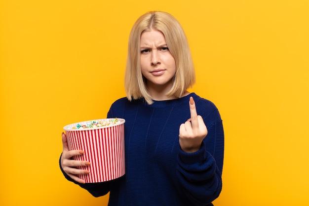 Blonde vrouw voelt zich boos, geïrriteerd, opstandig en agressief, draait de middelvinger om en vecht terug