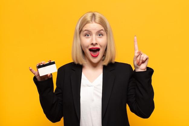 Blonde vrouw voelt zich een gelukkig en opgewonden genie na het realiseren van een idee, vrolijk vinger opstekend, eureka!
