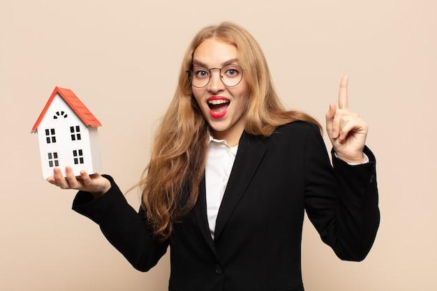 Blonde vrouw voelt zich een gelukkig en opgewonden genie nadat ze een idee heeft gerealiseerd