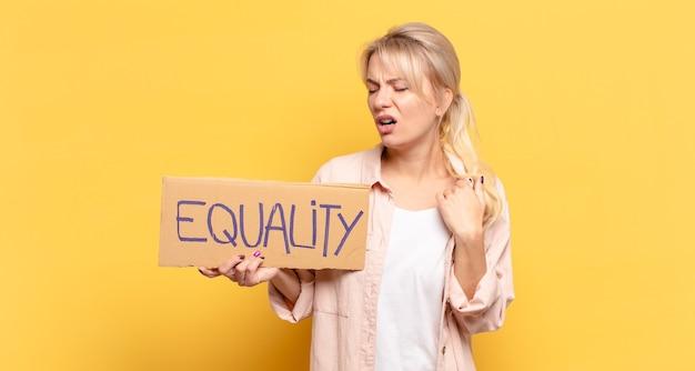 Blonde vrouw voelt zich gefrustreerd en houdt een bordje vast met de tekst: gelijkheid
