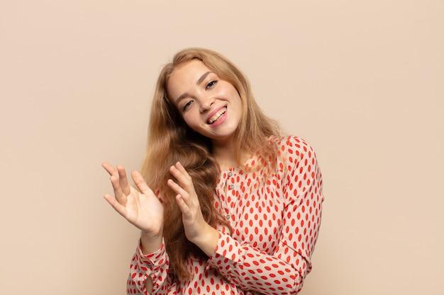 Blonde vrouw voelt zich gelukkig en succesvol, lacht en klapt in de handen, zegt gefeliciteerd met een applaus