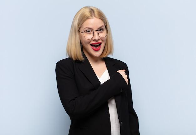 Blonde vrouw voelt zich gelukkig, positief en succesvol, gemotiveerd wanneer ze voor een uitdaging staat of goede resultaten behaalt