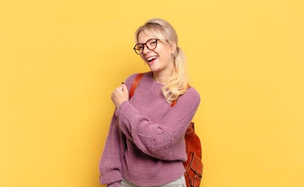 Blonde vrouw voelt zich gelukkig, positief en succesvol, gemotiveerd wanneer ze voor een uitdaging staat of goede resultaten viert