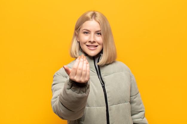 Blonde vrouw voelt zich gelukkig, succesvol en zelfverzekerd, staat voor een uitdaging en zegt kom maar op! of je verwelkomen
