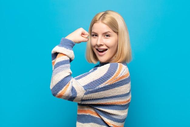 Blonde vrouw voelt zich gelukkig, tevreden en krachtig, buigt fit en gespierde biceps, ziet er sterk uit na de sportschool