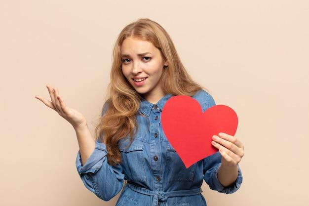 Blonde vrouw voelt zich gelukkig, verrast en opgewekt, glimlacht met een positieve houding en realiseert een oplossing of idee