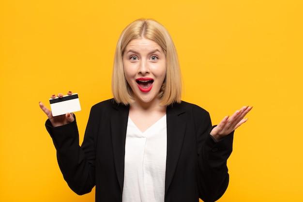 Blonde vrouw voelt zich gelukkig, verrast en opgewekt, glimlacht met een positieve houding, realiseert een oplossing of idee