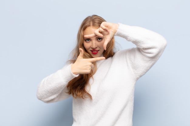 Blonde vrouw voelt zich gelukkig, vriendelijk en positief, lacht en maakt een portret of fotolijst met handen