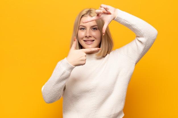 Blonde vrouw voelt zich gelukkig, vriendelijk en positief, lacht en maakt een portret of fotolijstje met handen
