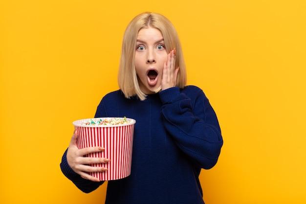 Blonde vrouw voelt zich geschokt en bang, kijkt doodsbang met open mond en handen op de wangen