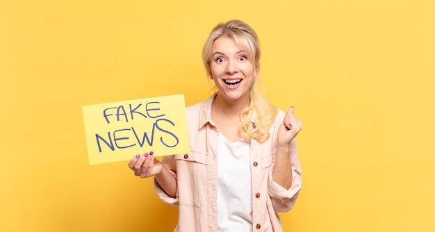 Blonde vrouw voelt zich geschokt, opgewonden en blij, lacht en viert succes, zeggend wow!