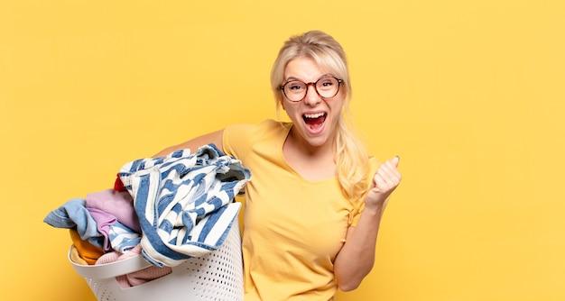 Blonde vrouw voelt zich geschokt, opgewonden en gelukkig, lacht en viert succes, zeggend wow!
