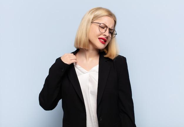 Blonde vrouw voelt zich gestrest, angstig, moe en gefrustreerd, trekt de hals van het shirt aan en kijkt gefrustreerd door het probleem