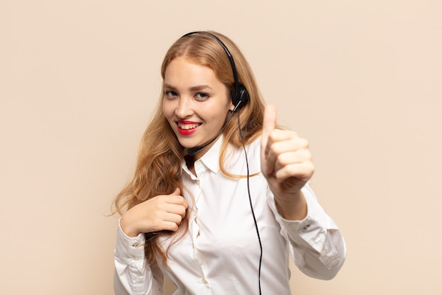 Blonde vrouw voelt zich trots, zorgeloos, zelfverzekerd en gelukkig, positief glimlachend met duimen omhoog