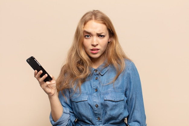 Blonde vrouw voelt zich verbaasd en verward, met een domme, verbijsterde uitdrukking op zoek naar iets onverwachts