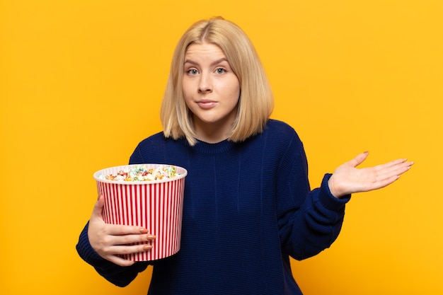 Blonde vrouw voelt zich verbaasd en verward, twijfelt, weegt of kiest verschillende opties met een grappige uitdrukking