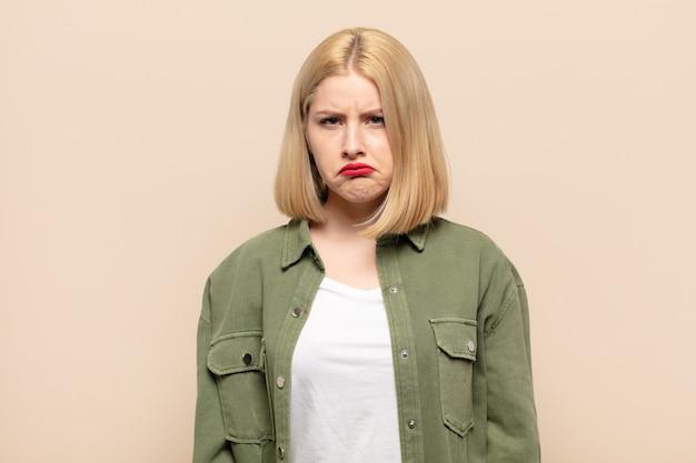 Blonde vrouw voelt zich verdrietig en zeurt met een ongelukkige blik, huilt met een negatieve en gefrustreerde houding