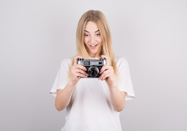 Blonde vrouw vreugdevol verrast kijken naar een retro camera