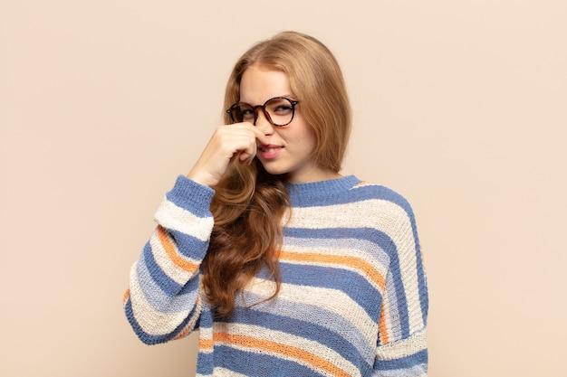 Blonde vrouw walgt en houdt neus vast om te voorkomen dat ze een vieze en onaangename stank ruikt