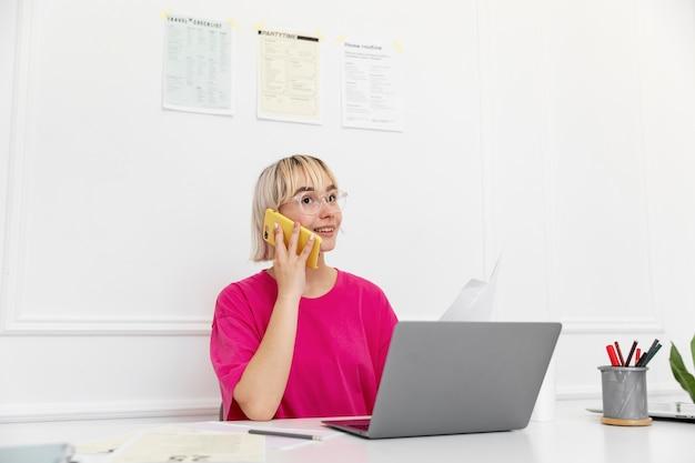 Blonde vrouw werkt vanuit huis op haar laptop