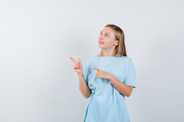 Blonde vrouw wijst naar rechts met wijsvingers in blauw t-shirt en ziet er schattig uit