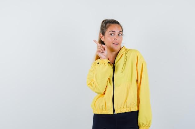 Blonde vrouw wijsvinger opheffen in eureka gebaar terwijl wegkijken in geel bomberjack en zwarte broek en gelukkig kijken