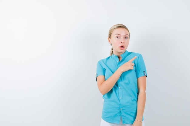 Blonde vrouw wijzend op de rechter bovenhoek in blauwe blouse geïsoleerd
