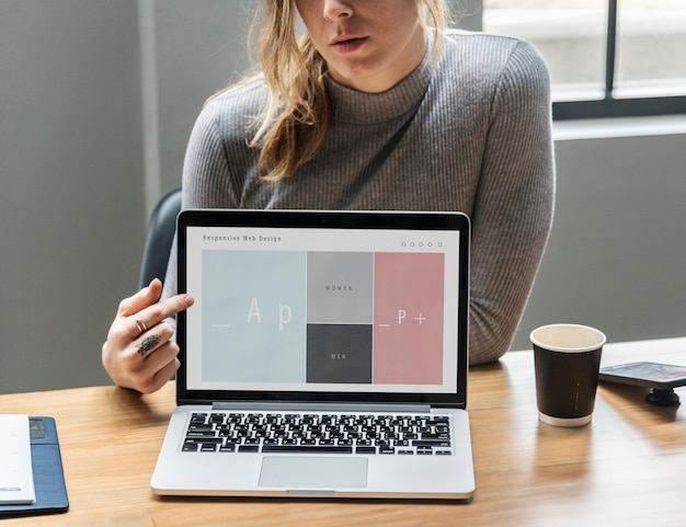 Blonde vrouw wijzend op een laptop scherm