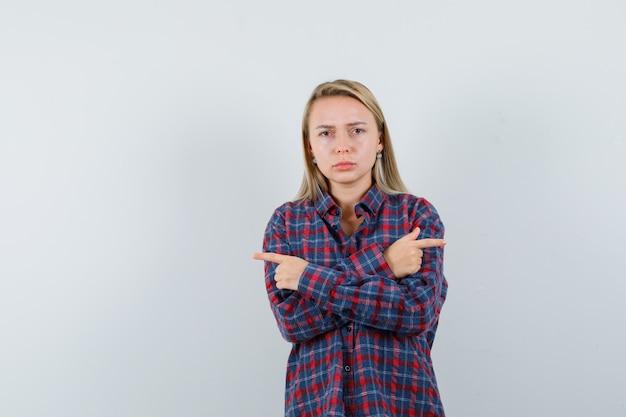 Blonde vrouw wijzend op verschillende richtingen met wijsvingers in geruit overhemd en op zoek naar ernstige, vooraanzicht.