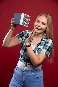 Blonde vrouw wordt blijer en verrast als ze een geschenkdoos ontvangt.