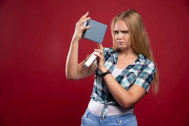 Blonde vrouw wordt verdrietig en verward bij het openen van een geschenkdoos.