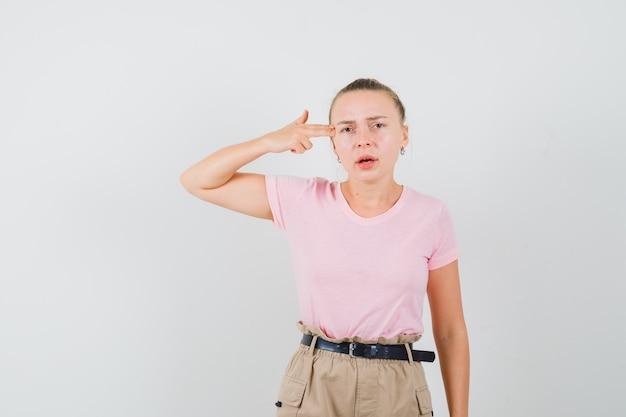 Blonde vrouw zelfmoord gebaar maken in t-shirt, broek en op zoek naar ernstige, vooraanzicht.