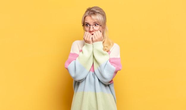 Blonde vrouw ziet er bezorgd, angstig, gestrest en bang uit, bijt nagels en kijkt naar laterale kopieerruimte