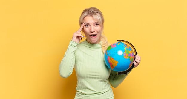 Blonde vrouw ziet er blij, verbaasd en verrast uit, lacht en realiseert zich geweldig en ongelooflijk goed nieuws