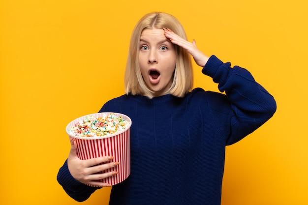 Blonde vrouw ziet er blij, verbaasd en verrast uit, lacht en realiseert zich verbazingwekkend en ongelooflijk goed nieuws
