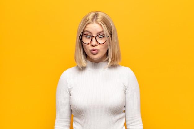 Blonde vrouw ziet er goofy en grappig uit met een dwaze schele uitdrukking, een grapje en gek rond