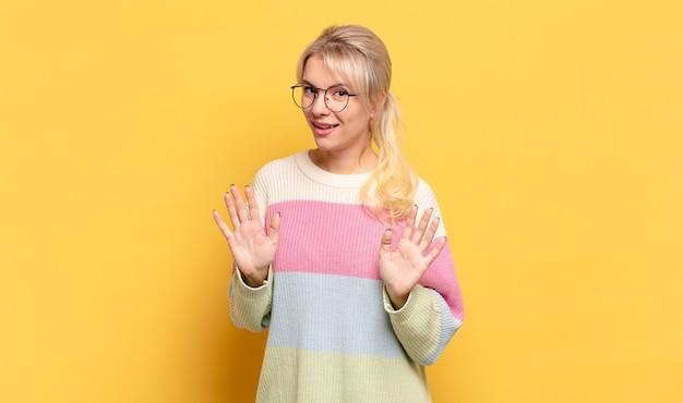 Blonde vrouw ziet er nerveus, angstig en bezorgd uit, zegt niet mijn schuld of ik heb het niet gedaan