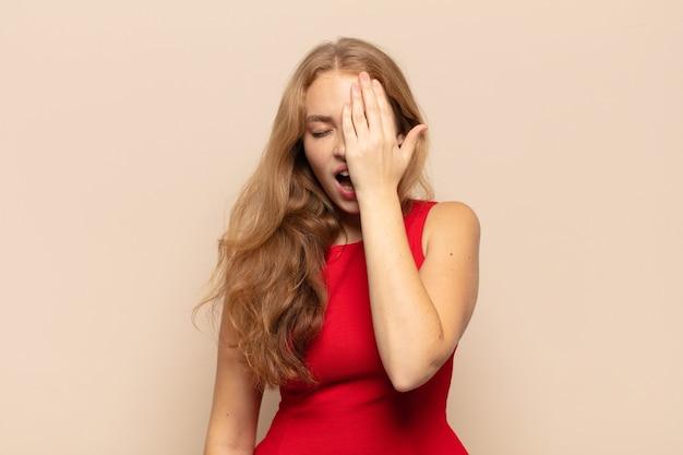 Blonde vrouw ziet er slaperig, verveeld en geeuwend uit, met hoofdpijn en een hand die de helft van het gezicht bedekt