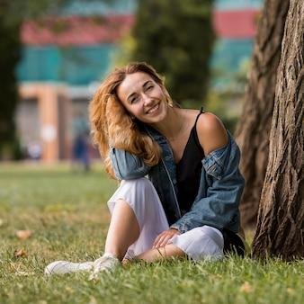 Blonde vrouw zit naast een boom